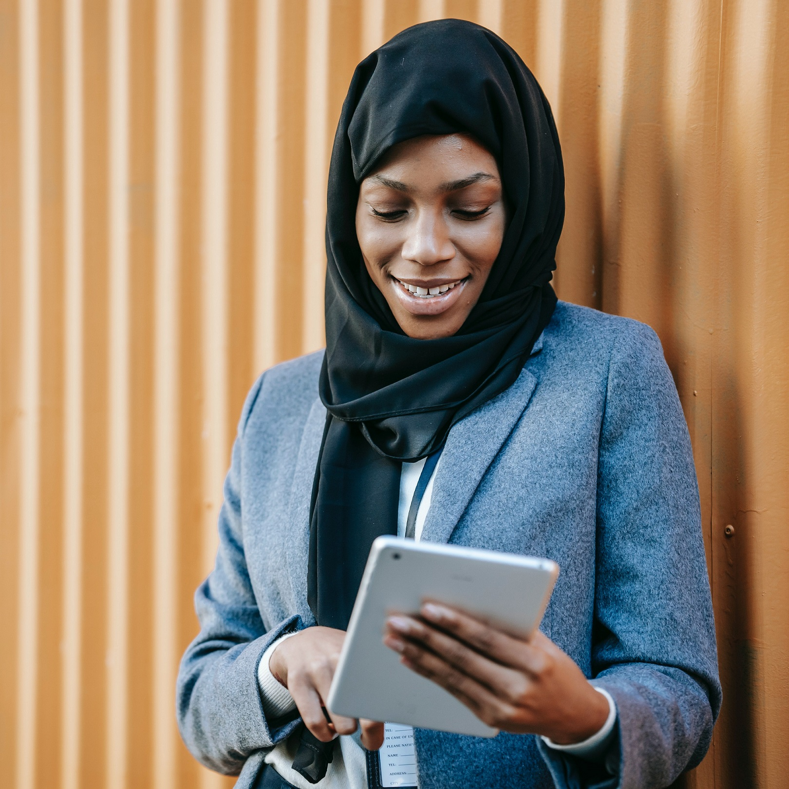 African woman smiles while in business attire, using her tablet.