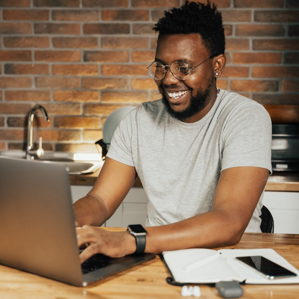 African intern works at his laptop, smiling.