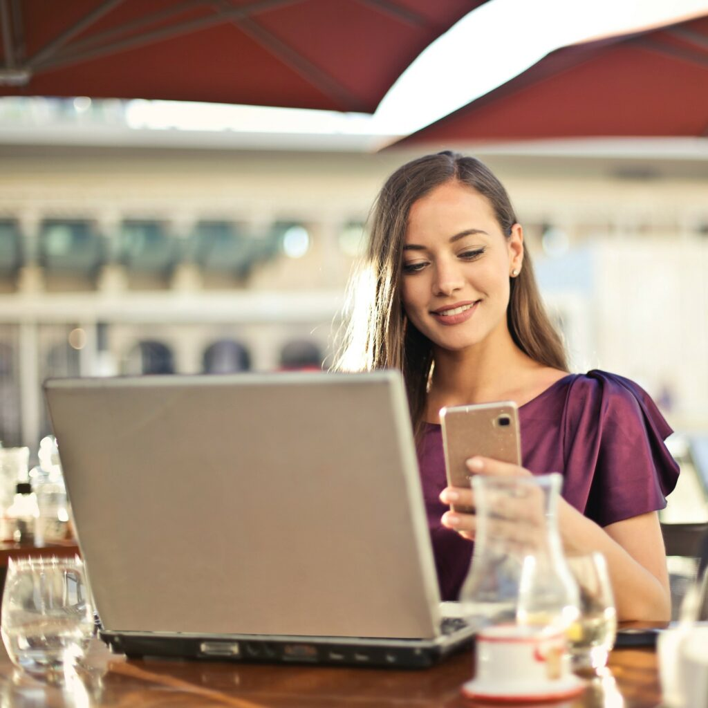Intern sits at a cafe in front of her laptop and smartphone.