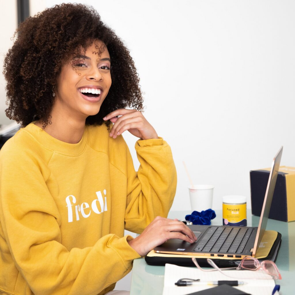 A smiling intern sits at her home office in front of her laptop.